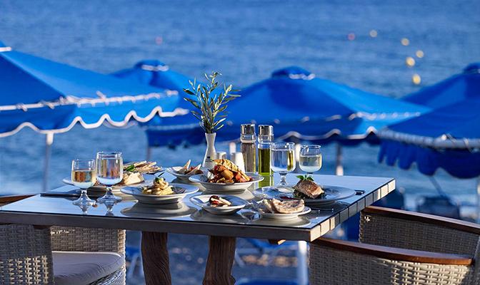 Tafel met gerechte aan zee en blauwe parasols
