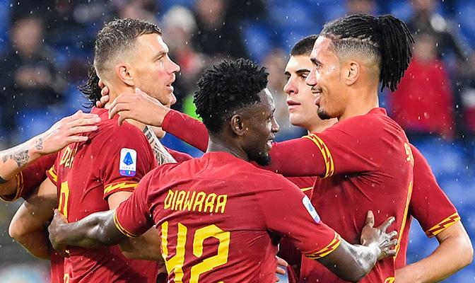 Voetbalspelers van AS Roma die elkaar omhelzen op het veld