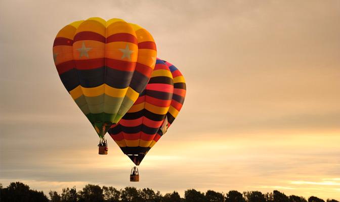 2 multicolor luchtbalonnen en ondergaande zon